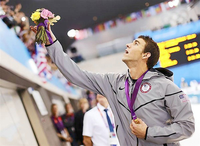 Michael Phelps of the U.S. throws his winner's flower bouquet to his mother Debbie (not pictured), after receiving his gold medal after winning the men's 4x100m medley relay final during the London 2012 Olympic Games at the Aquatics Centre