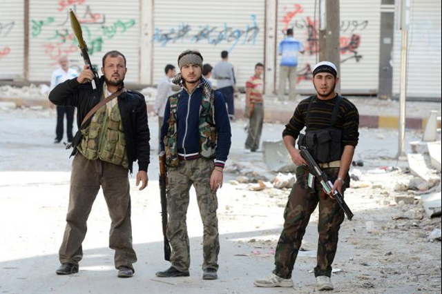 Armed rebel fighters at the front line as they battle pro-government Syrian troops. (Getty Images)