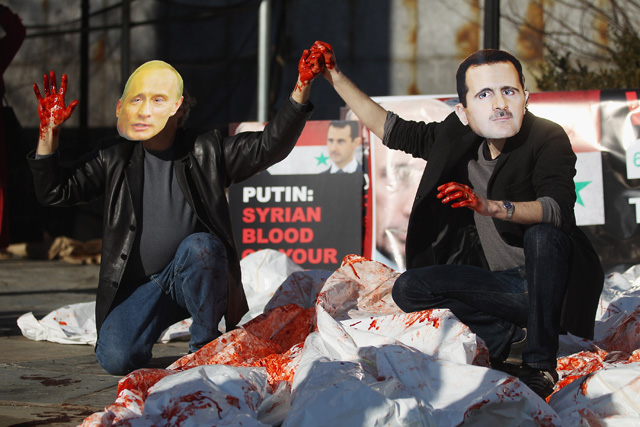 Actors wearing masks of Syrian President Bashar al-Assad and Russian Prime Minister Vladimir Putin perform with body bags during a demonstration outside United Nations headquarters on January 24, 2011 in New York City.