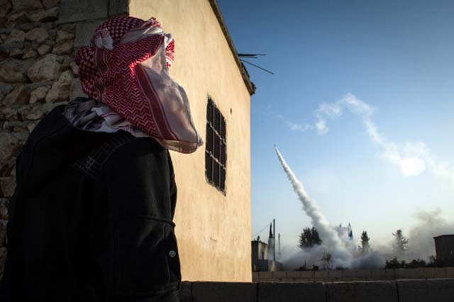A Rebel fighter watches a rocket headed for destruction in the city of Aleppo / Getty Images