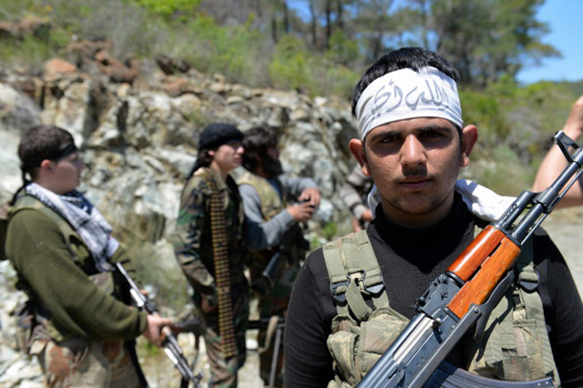 Rebel fighters from the Al-Ezz bin Abdul Salam Brigade attend a training session at an undisclosed location near the al-Turkman mountains, in Syria's northern Latakia province/ Getty Images