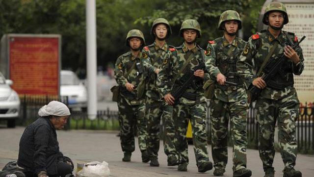 Muslim Uighur woman begs as armed Chinese paramilitary police march past on a street in Urumqi, the capital of the Xinjiang region,( GETTY)