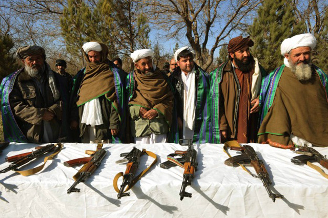 Taliban fighters stand near their weapons after they joined Afghanistan government forces during a ceremony in Herat (Getty Images)