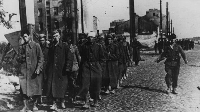 1st October 1944:  The end of Warsaw's uprising sees a group of city defenders marched off to prison camps by their German captors.  (Getty Images)