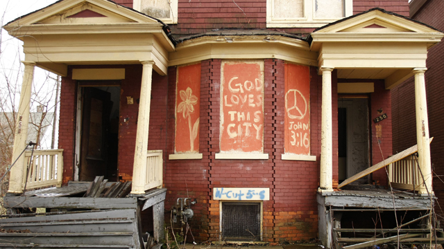 """The words, """"God Loves This City"""" are painted on the front of an abandoned home in Detroit  (Getty Images)"""