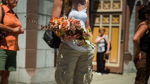 A woman brings a bouquet of flowers to a public vigil at the Presbyteres-Eglises in Lac-Megantic, Quebec, Canada (Getty Images)