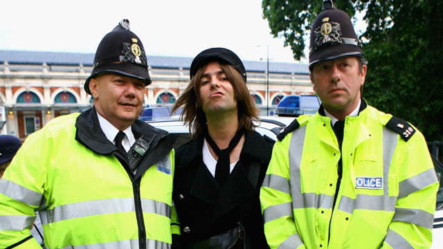 Singer Liam Gallagher poses for a photograph with two policemen (Getty Images)