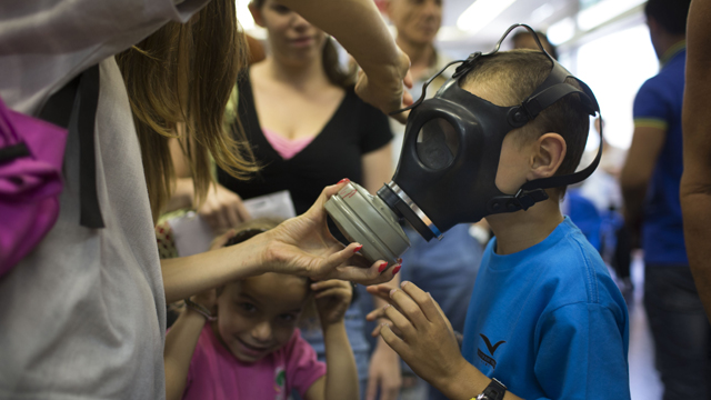 Israeli children learn to use a gas mask among raising concerns in the Middle East. (Getty)