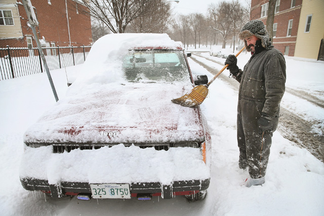 Ferdinand Barrios clears snow from his truck in the Humboldt Park neighborhood on January 2 in Chicago. The city was hit by a massive winter storm that is now bearing down on the Northeast. (Getty)