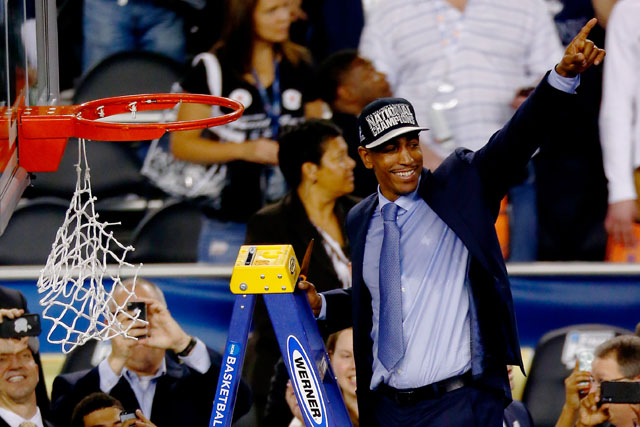 Kevin Ollie points to the crowd as he prepares to cut down the net following UConn's championship game win over Kentucky. (Getty)