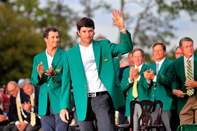 Watson waves to the crowd after 2013 champion Adam Scott presented Watson with the Green Jacket. (Getty)