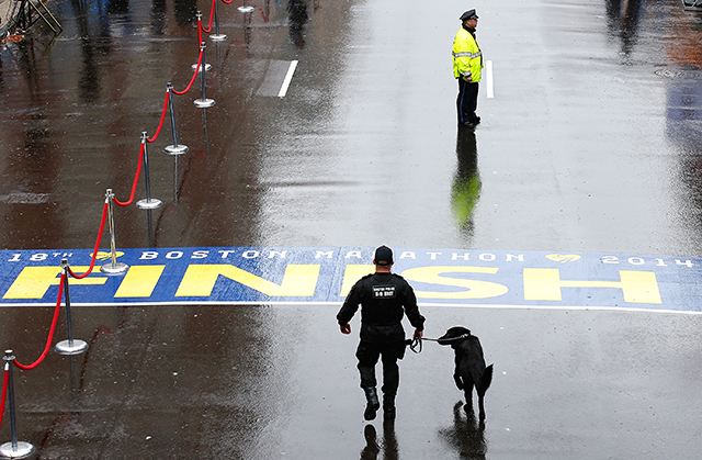 Boston Police officers and a K-9 unit patrol the finish line of the Boston Marathon prior to the flag raising ceremony Tuesday commemorating the one-year anniversary of the Boston Marathon bombings. (Getty)