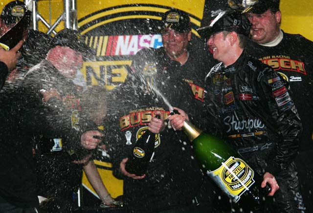 Kurt Busch sprays team members with champagne after a victory in the Spring Series. (Getty)