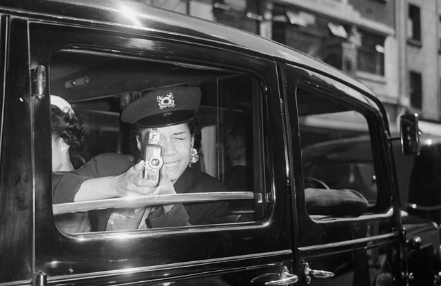 Edna Mae Robinson, wife of the American boxer, Sugar Ray Robinson, using a cine camera from the back of a car in 1952. (Getty)
