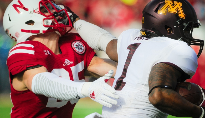 Minnesota's KJ Maye stiffarms Nebraska's Nate Gerry in an attempt to elude a tackle on Saturday afternoon. (Getty)