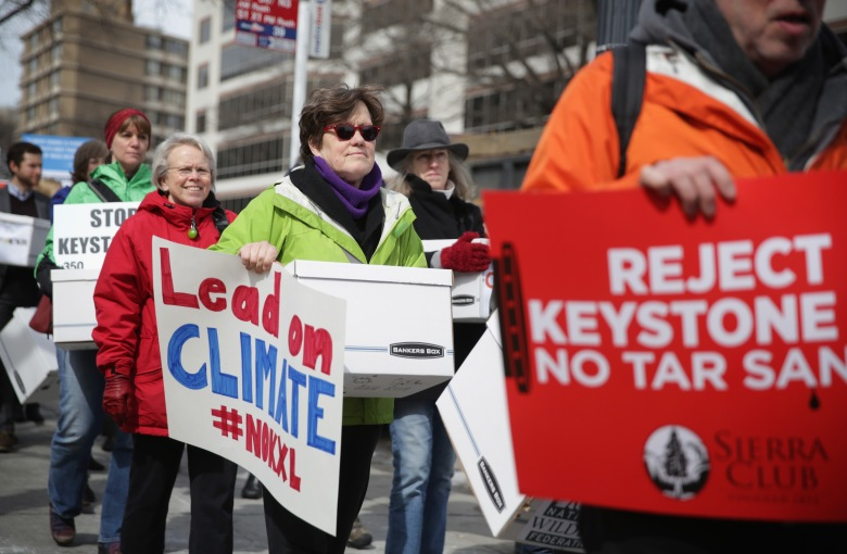 Activists carry signs and petition boxes as they march to the State Department for a rally to protest against the Keystone XL pipeline March 7, 2014 in Washington, DC. (Getty)