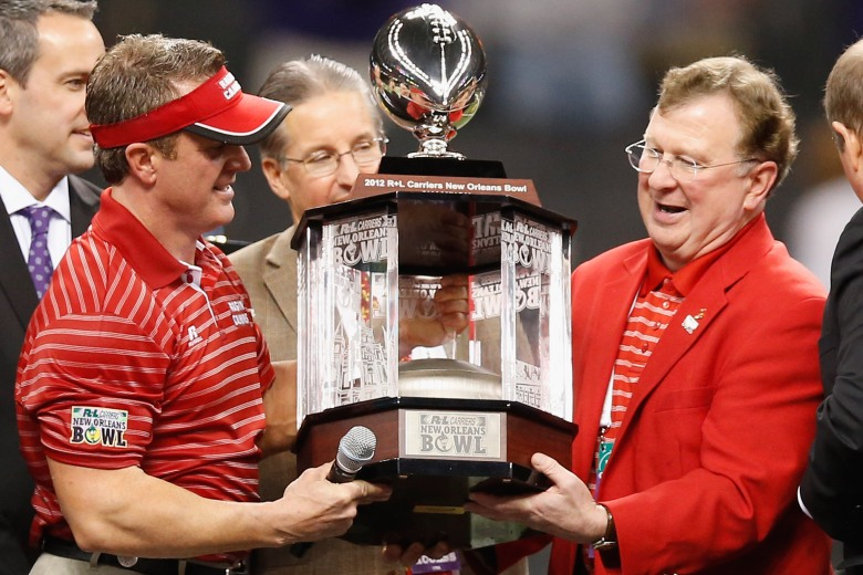 Ragin' Cajuns coach Mark Hudspeth (left) accepts the New Orleans Bowl trophy after the 2012 game. (Getty)