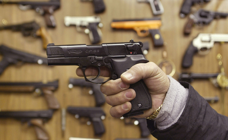 A man holds an Airsoft plastic BB gun in front of a shop display of the hobbyist replica firearms January 6, 2003 in London. (Getty)