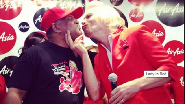 Richard Branson (R), dressed as a female flight attendant, kisses Tony Fernandes. (Virgin.com)
