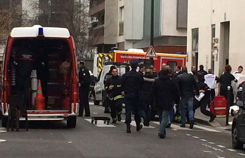 Emergency personnel at the scene outside of Charlie Hebdo's offices. (Getty)