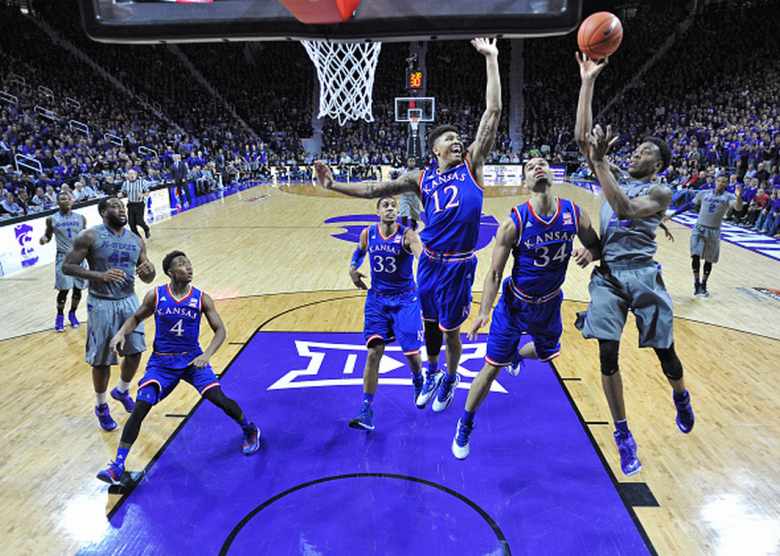 Guard Wesley Iwundu #25 of the Kansas State Wildcats puts up a shot against defenders Perry Ellis #34 and Kelly Oubre Jr. #12 of the Kansas Jayhawks during the first half on February 23, 2015 at Bramlage Coliseum in Manhattan, Kansas. (Getty)
