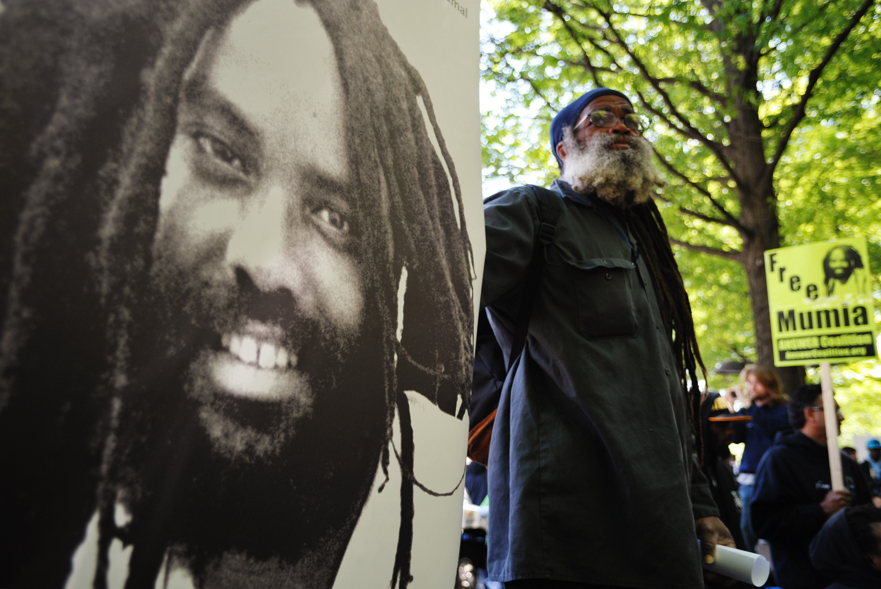 A protester stands next to an image of Mumia Abu-Jamal  outside the US Department of Justice  on April 24, 2012 in Washington, DC. (Getty)