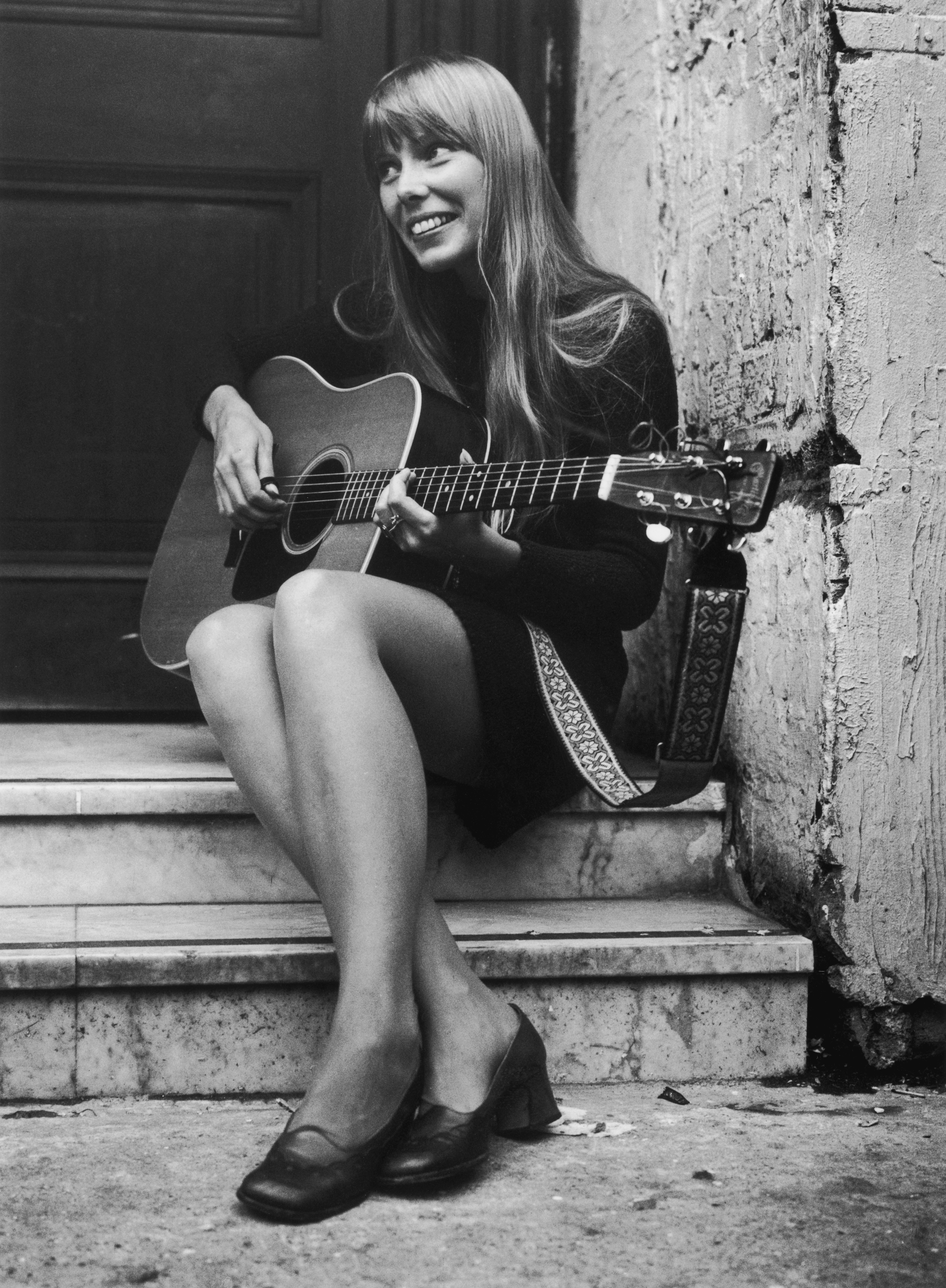 Canadian folk singer and songwriter Joni Mitchell, strumming her guitar outside The Revolution club in London. in 1968 (Getty)