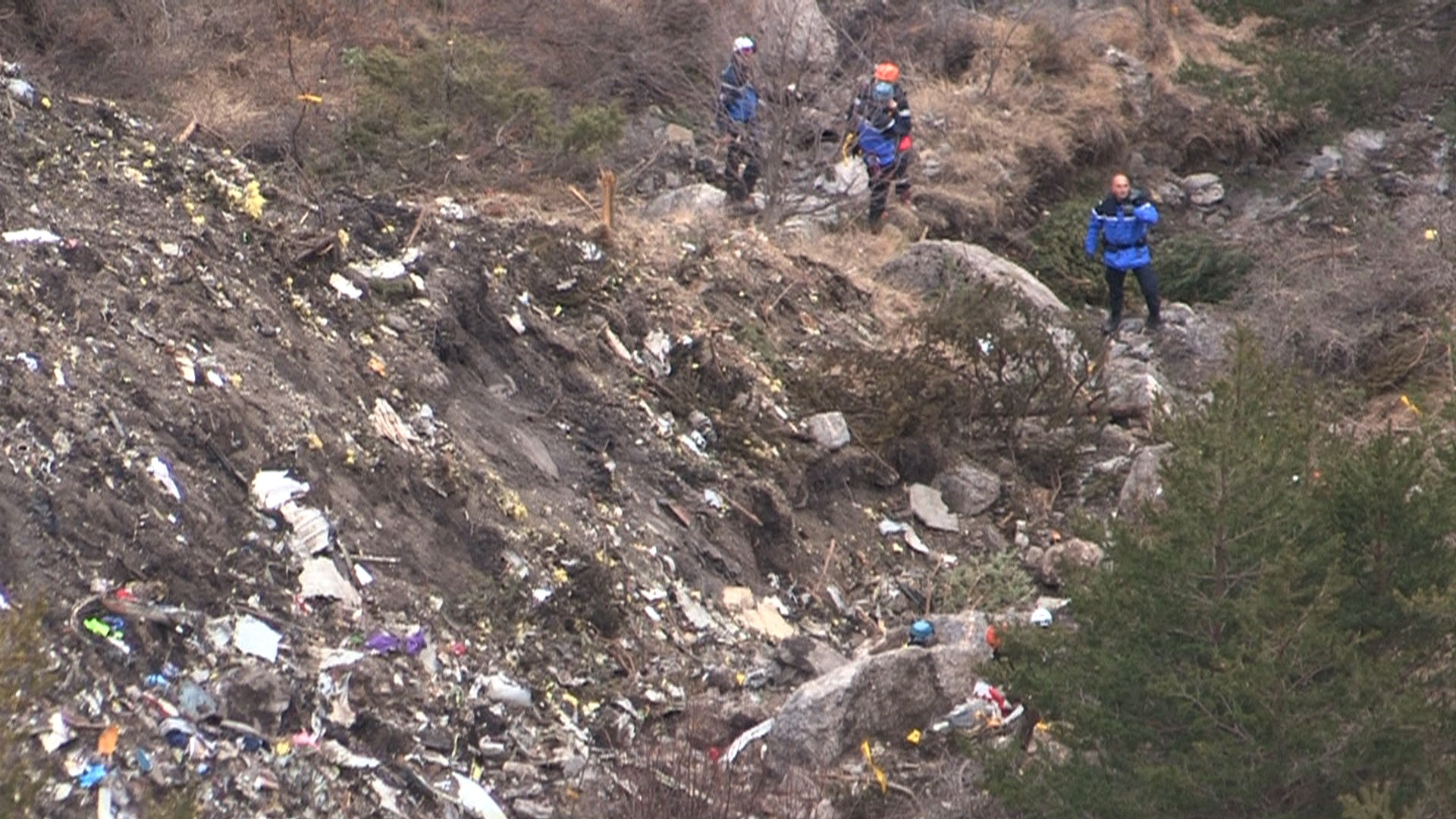 A screengrab taken from an AFP TV video on March 24, 2015 shows search and rescue personnel near scattered debris while making their way through the crash site of the Germanwings Airbus A320 that crashed in the French Alps above the southeastern town of Seyne. The plane, which had taken off from Barcelona in Spain and was headed for Dusseldorf in Germany, crashed earlier in the day with 150 people onboard. (Getty)