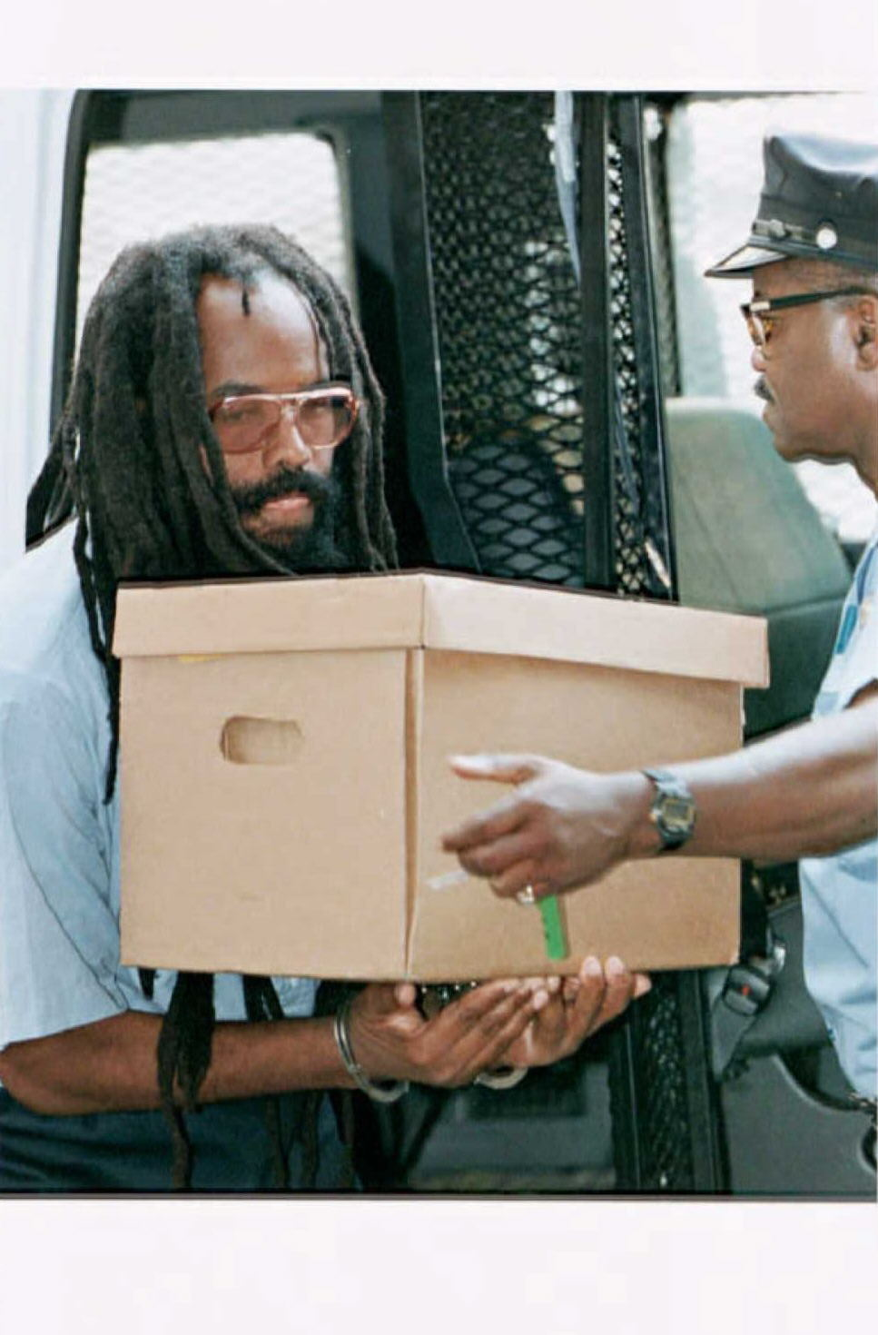 Mumia Abu-Jamal carries a box of legal documents as he enters City Hall in Philadelphia for his appeals hearing . (Getty)