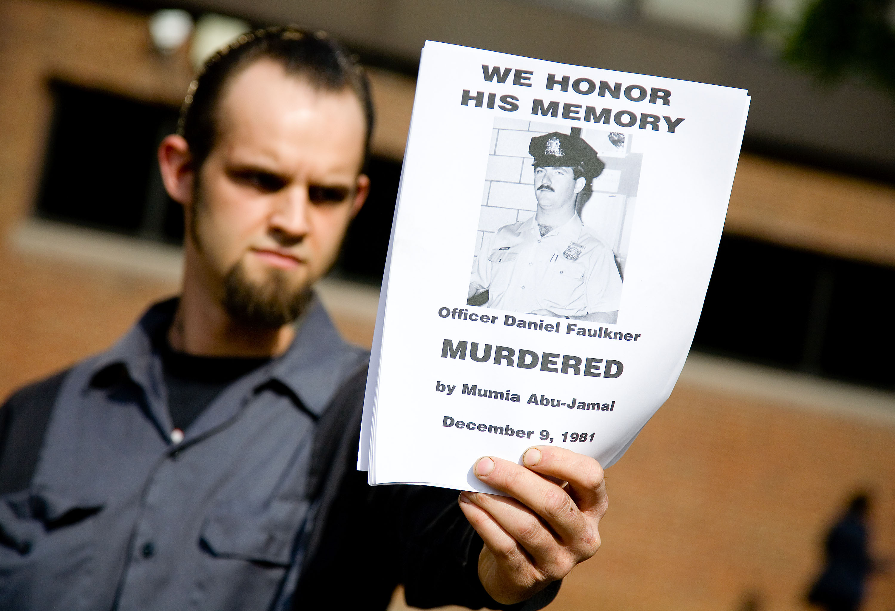 A counter protester holds a handbill in remembrance of slain police officer Daniel Faulkner at a rally for Faulker's convicted murderer,  death-row inmate Mumia Abu-Jamal outside the Federal Court building May 17, 2007 in Philadelphia, Pennsylvania.  (Getty)
