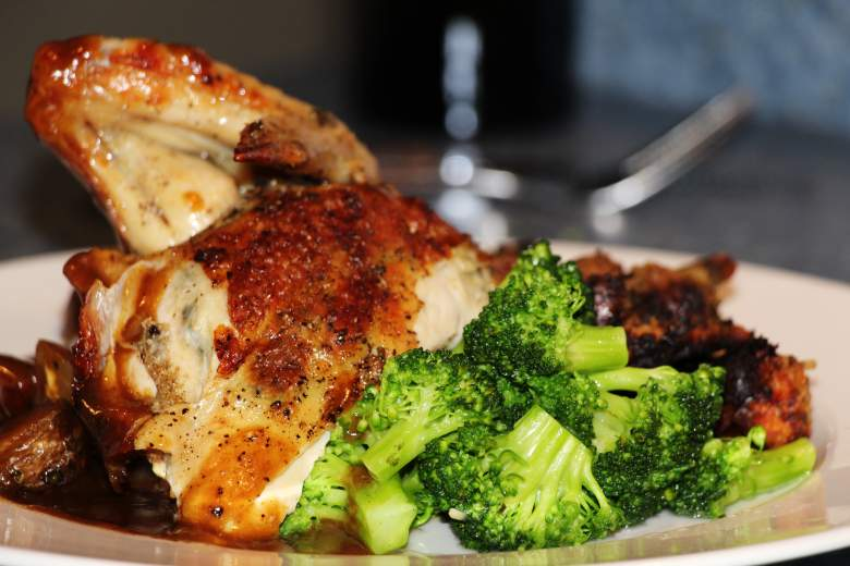 Image of roasted and seasoned chicken on a plate with broccoli, best homemade dog food