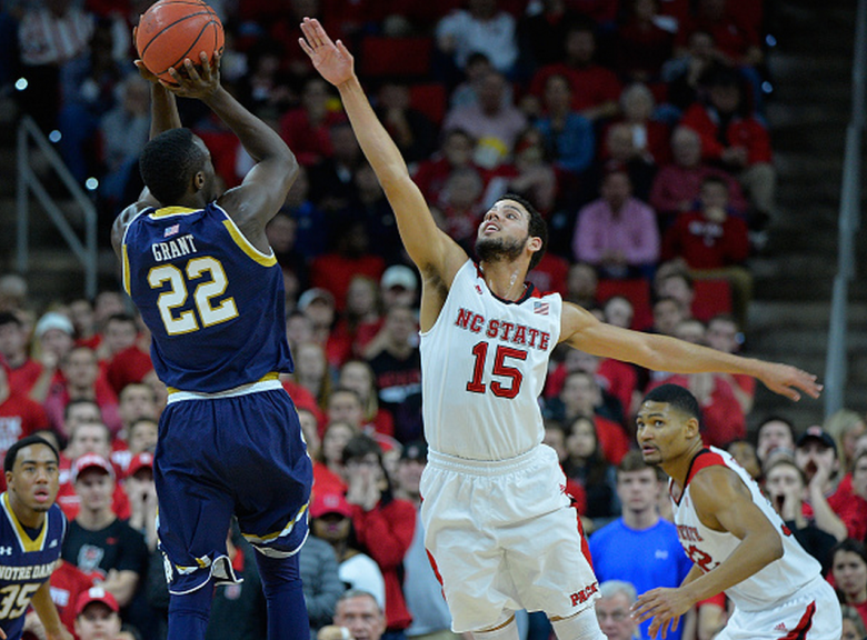 Cody Martin #15 of the North Carolina State Wolfpack challenges a shot by Jerian Grant #22 of the Notre Dame Fighting Irish during their game at PNC Arena on January 25, 2015 in Raleigh, North Carolina. Notre Dame won 81-78 in overtime. (Getty)