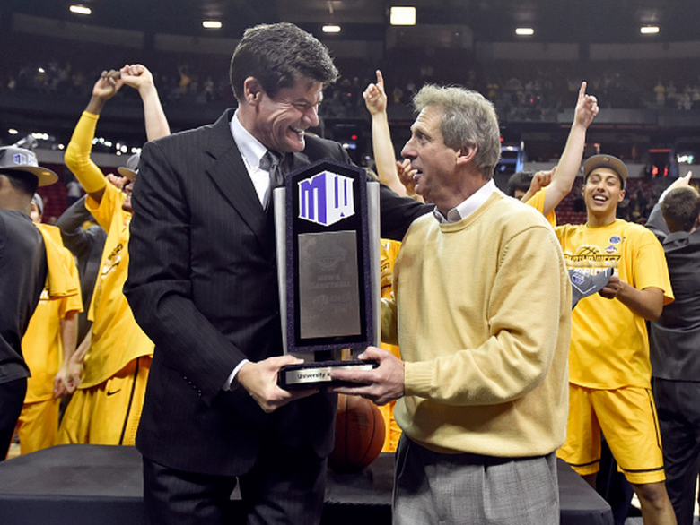 Mountain West Conference commissioner Craig Thompson (L) presents head coach Larry Shyatt (R) of the Wyoming Cowboys with the championship trophy after defeating the San Diego State Aztecs in the championship game of the Mountain West Conference basketball tournament at the Thomas & Mack Center on March 14, 2015 in Las Vegas, Nevada. Wyoming won 45-43. (Getty)