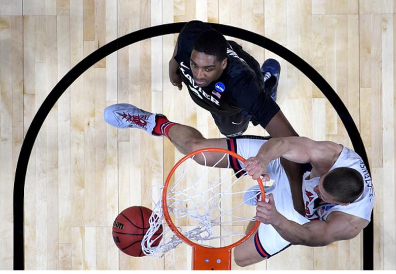 Arizona's Kaleb Tarczewski dunks the ball alongside Xavier's James Farr during the 2015 NCAA Men's Basketball Tournament. (Getty)