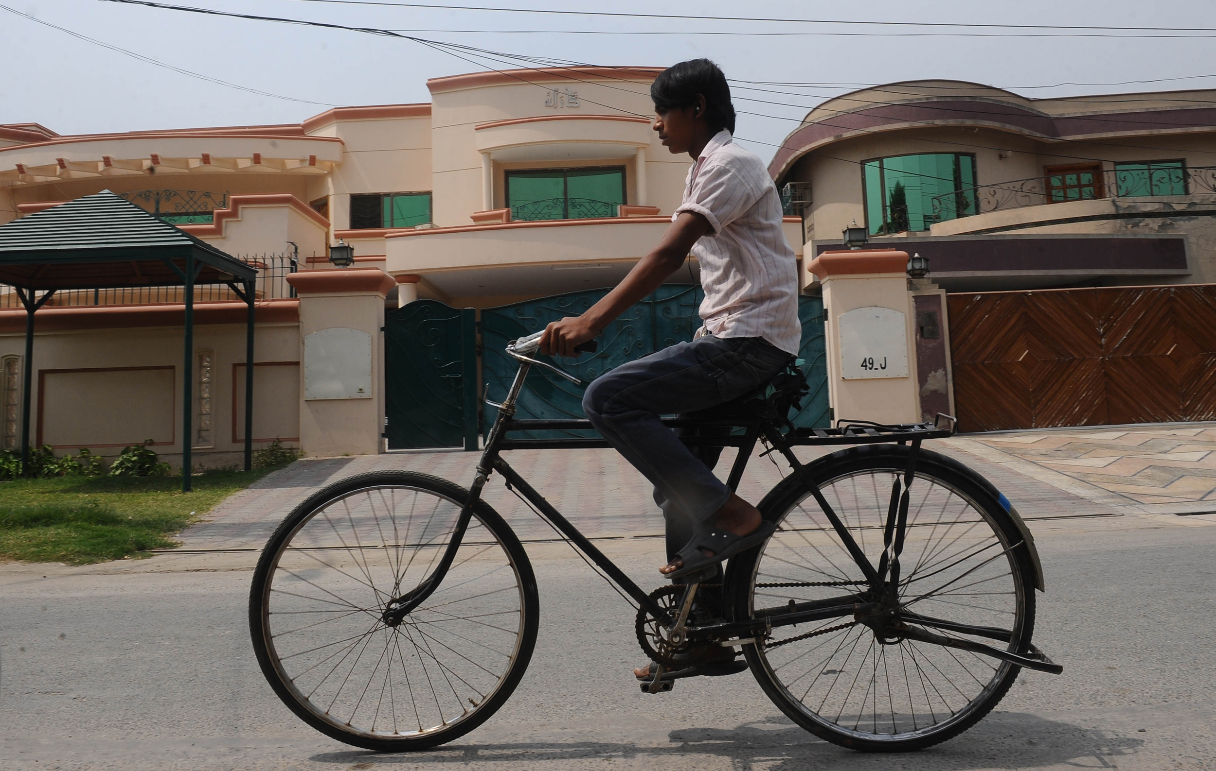 A Pakistani cyclist rides past Weinstein's house in Lahore on May 7, 2012.  Weinstein was killed in a U.S. drone strike in January 2015. (Getty)