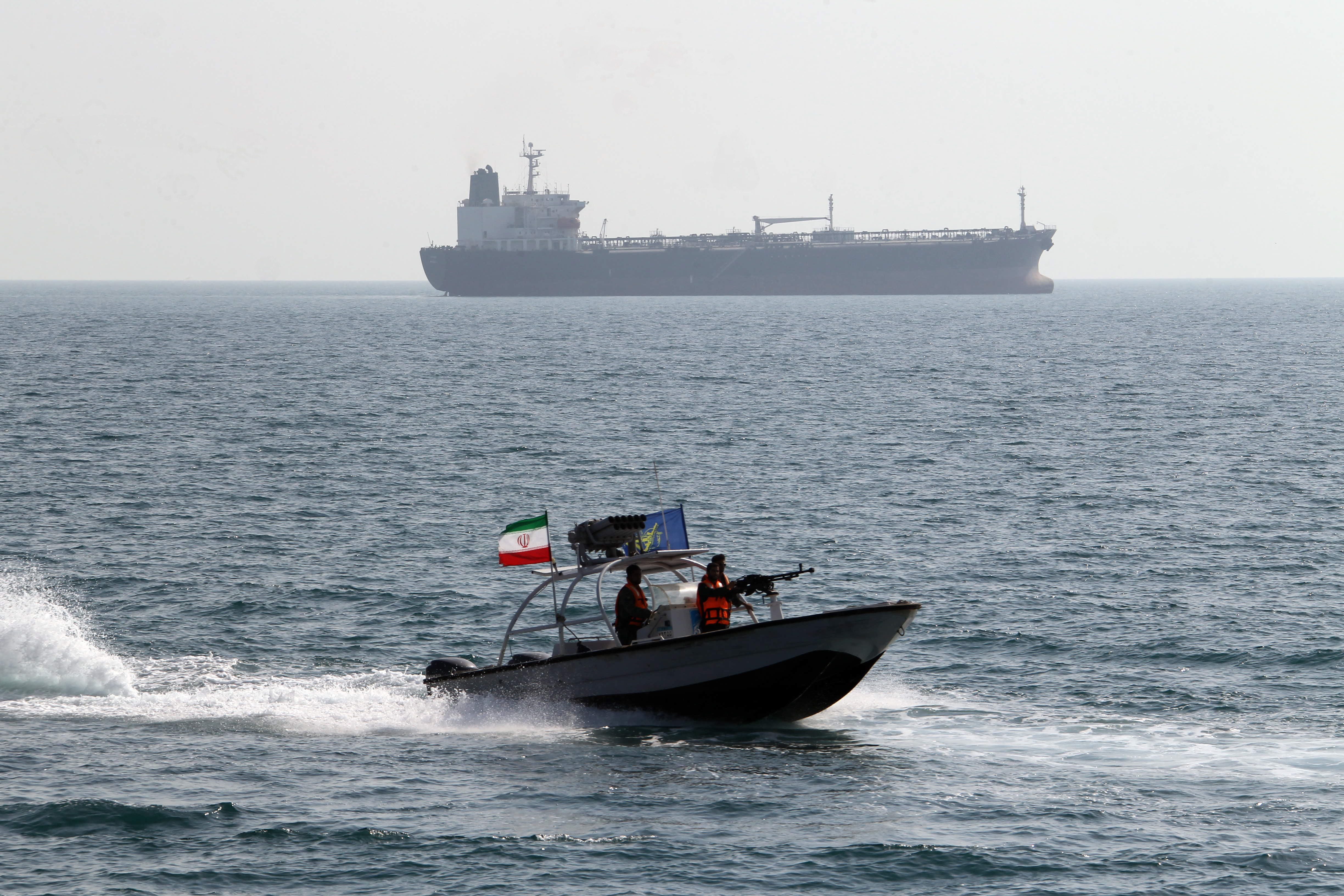 Iranian Revolutionary Guards drive a speedboat in front of an oil tanker during a ceremony to commemorate the 24th anniversary of the downing of Iran Air flight 655 by the US navy, at the port of Bandar Abbas on July 2, 2012.  (Getty)