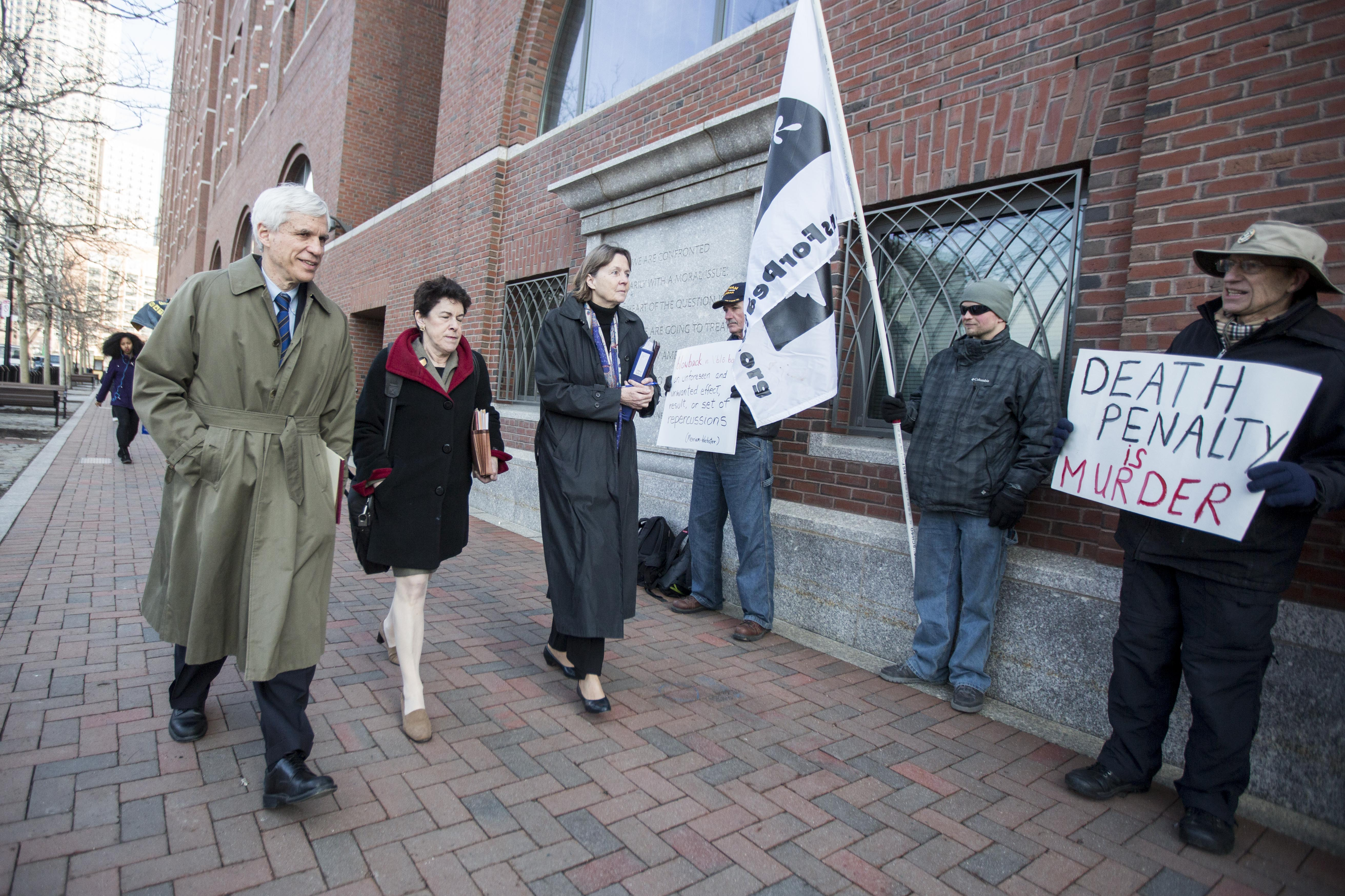 Members of the legal defense team for Boston Marathon bombing suspect Dzhokhar Tsarnaev, including David Bruck, (from left), Miriam Conrad, and Judy Clarke walk past death-penalty protesters at John Joseph Moakley United States Courthouse. (Getty)