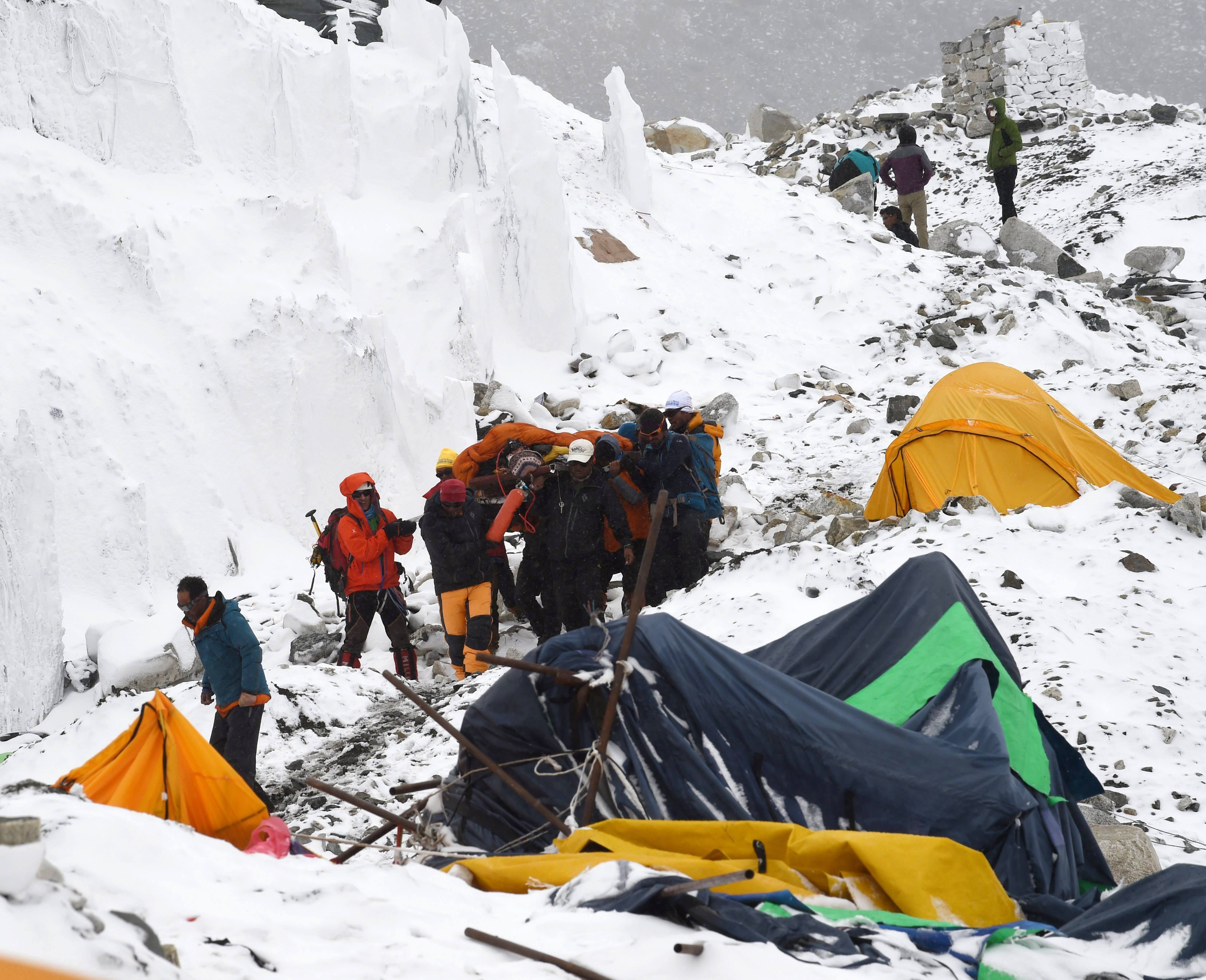 Rescuers carry an injured sherpa from the Mount Everest base camp after it was devastated by an avalanche triggered by a 7.8 magnitude earthquake that struck Nepal. (Getty)