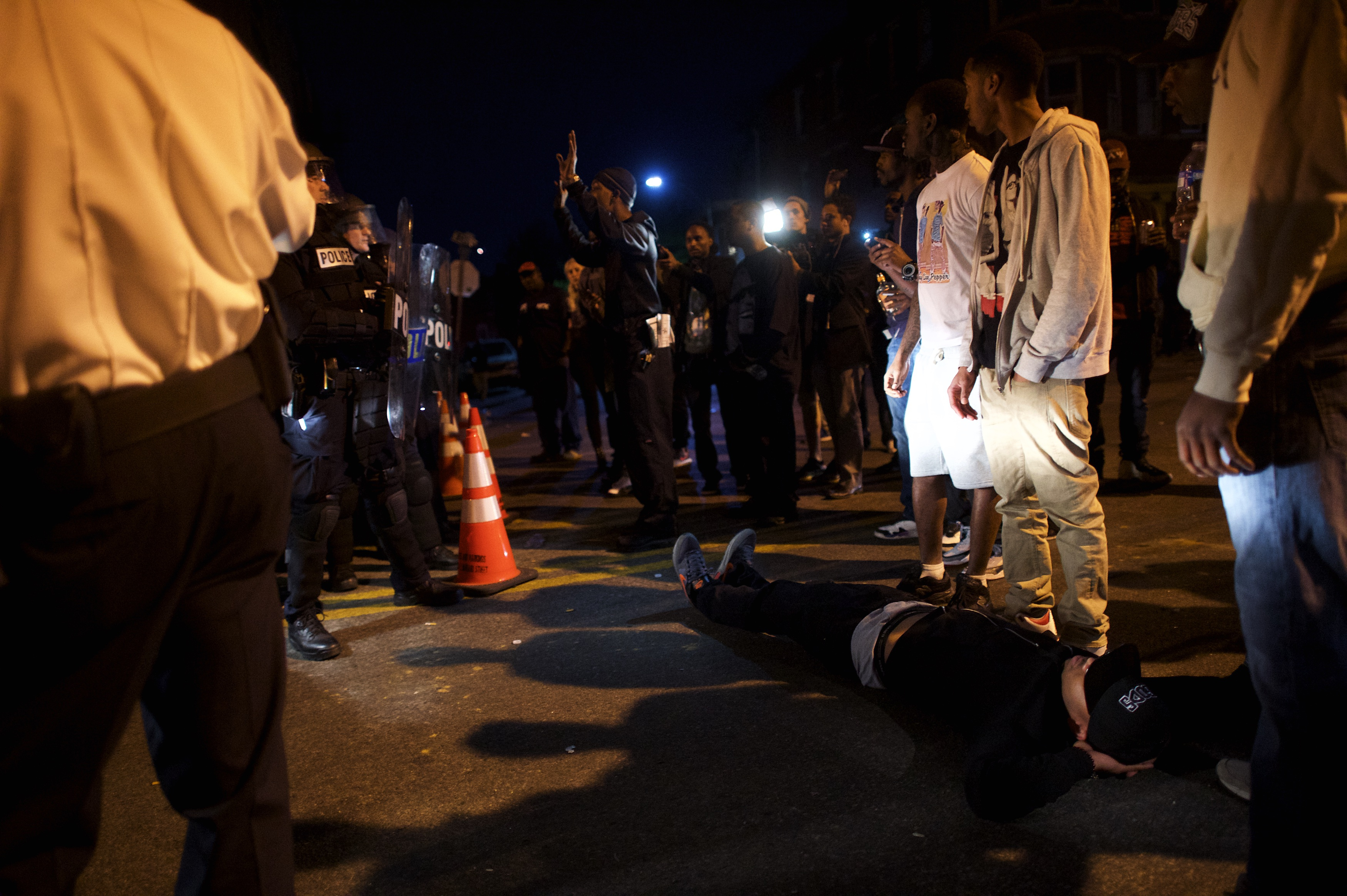 A protester lies in front of a police barricade blocking the exit of a vehicle. (Getty)