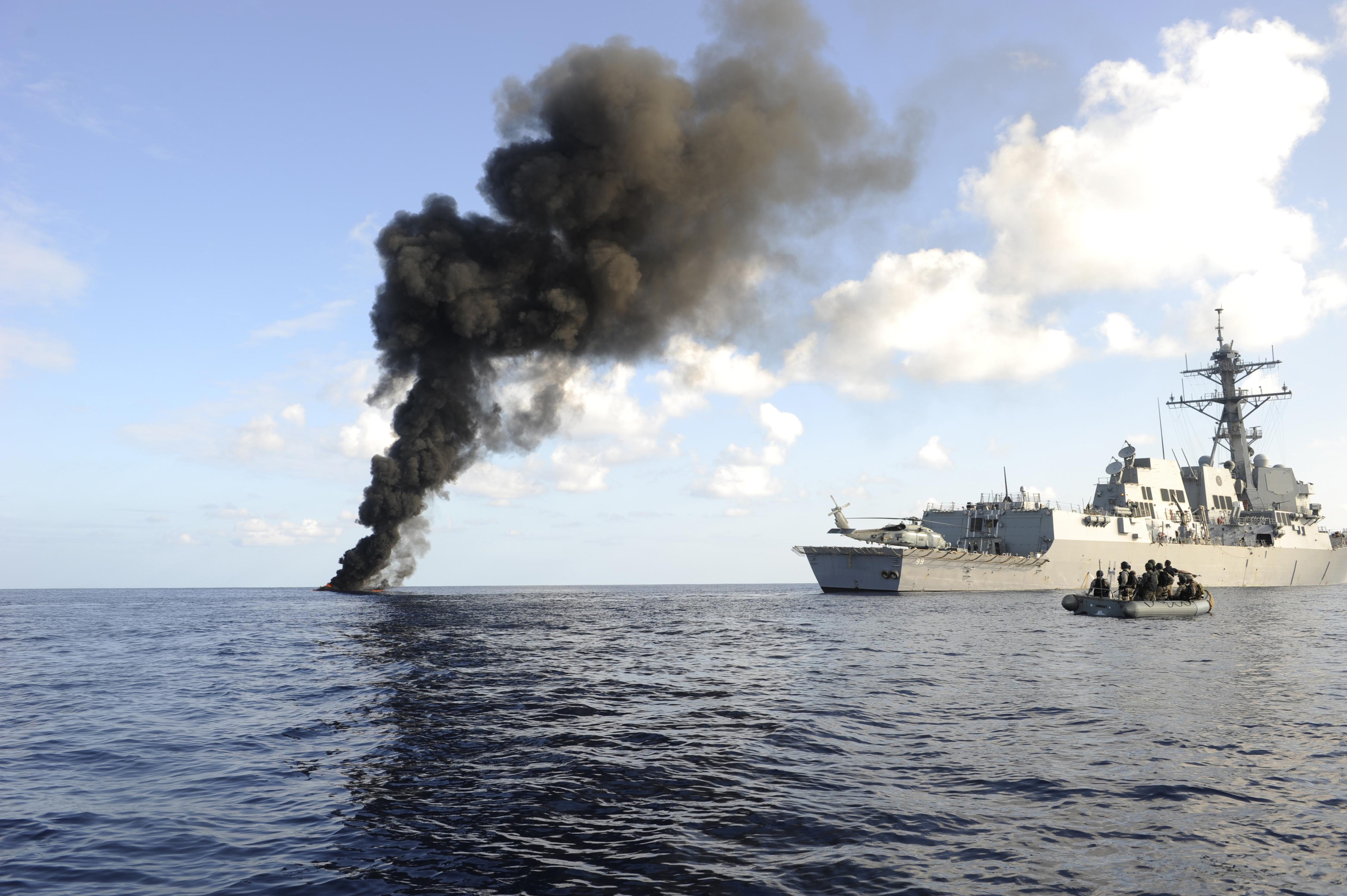 The Arleigh Burke-class guided missile destroyer USS Farragut (DDG 99) passes by the smoke from a suspected pirate skiff it disabled March 31, 2010 in the Gulf of Aden.  (Getty)