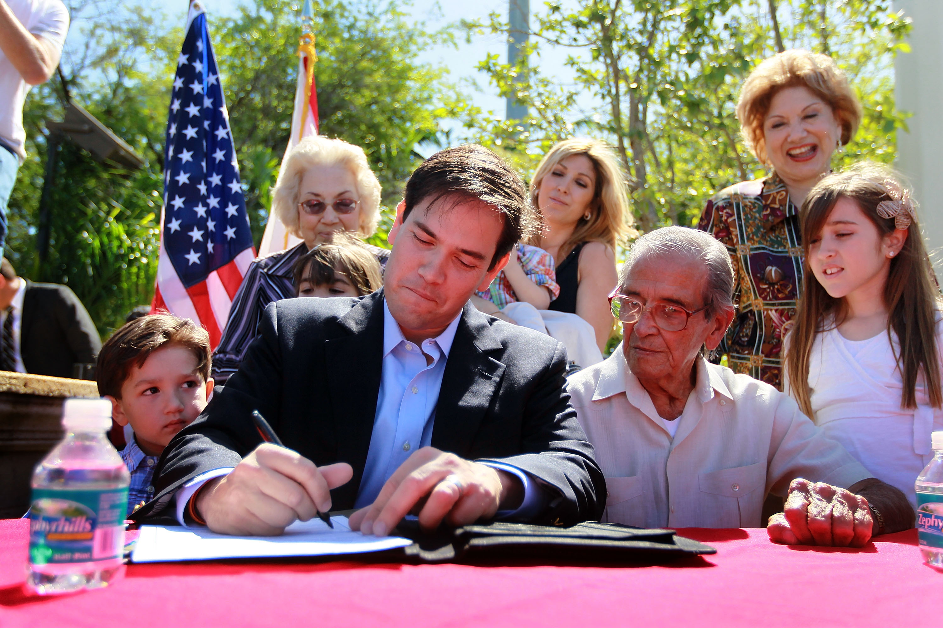 Marco Rubio (3rd L) puts pen to paper as he sits with his son, Anthony Rubio (L), father Mario Rubio (3rd R) and daughter Amanda Rubio (R) as he signs election documents officially qualifying him as a Republican candidate for the U.S. Senate on April 27, 2010 . (Getty)