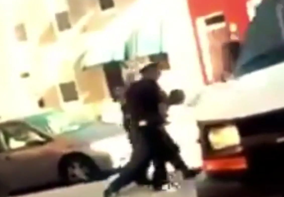 A screenshot from cell phone video taken by a bystander shows police dragging Freddie Gray toward the transport van.