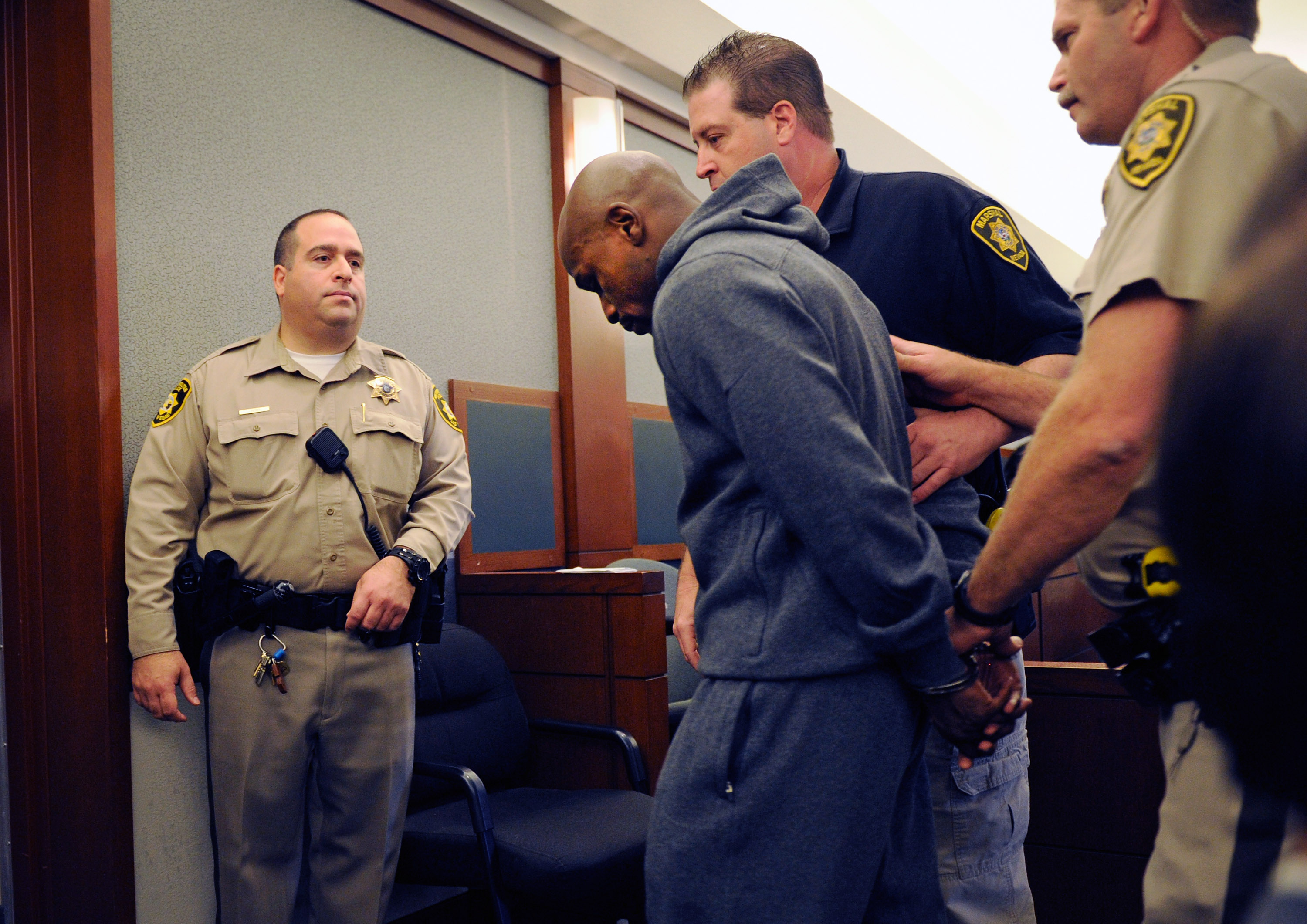 Maywether Jr. is lead away in handcuffs at the Clark County Regional Justice Center as he surrenders to serve a three-month jail sentence in 2012. (Getty)