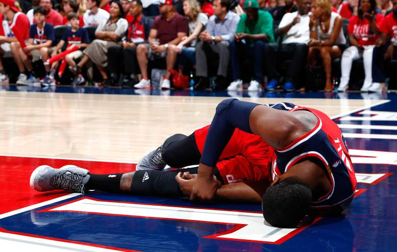 John Wall of the Wizards grabs his hand in pain after breaking it in Game 1 vs. the Hawks. (Getty)