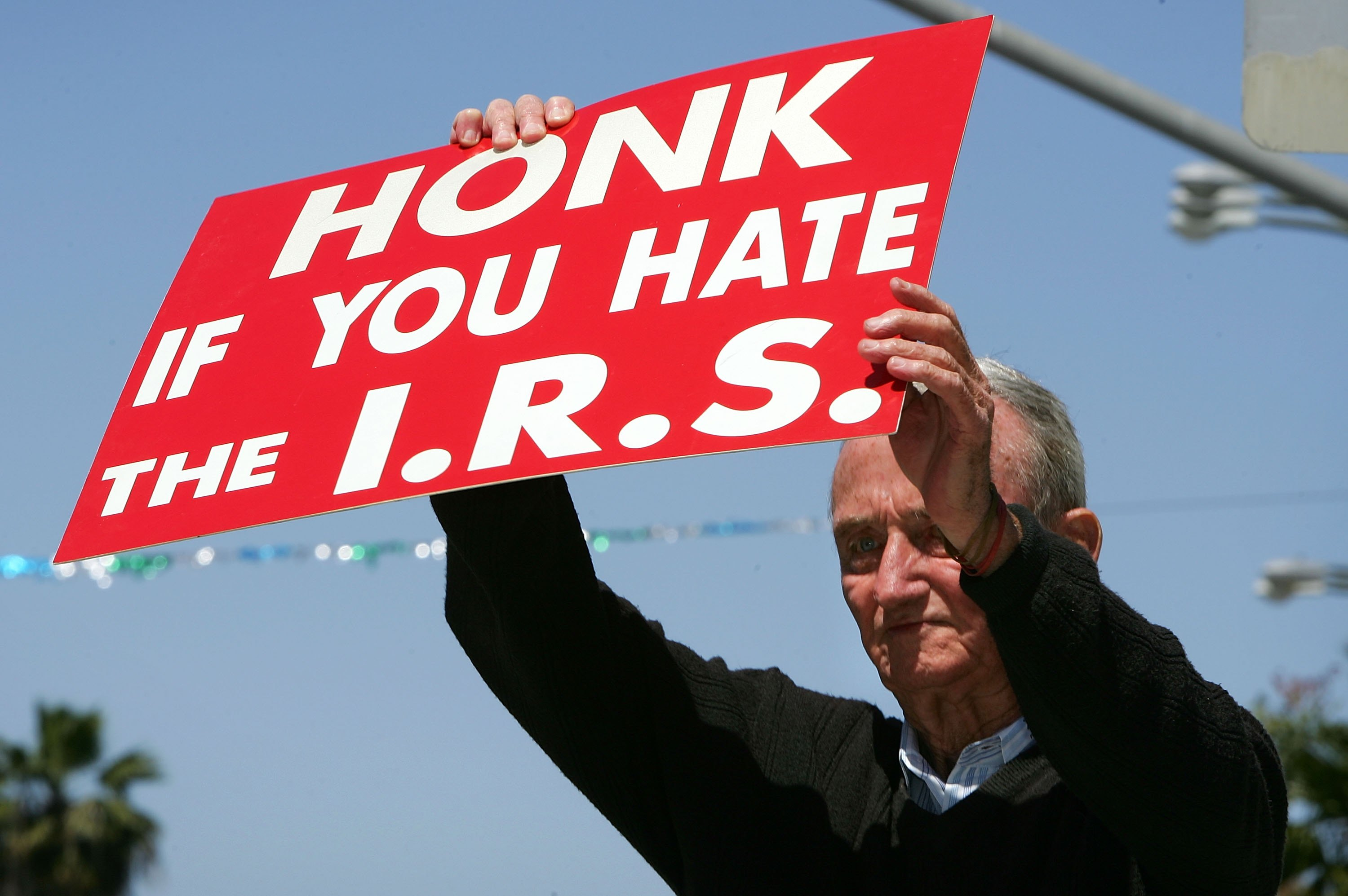 An anti-IRS protester holds a sign up at a rally. (Getty)