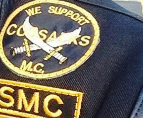 "Part of a Scimitars leather shows a ""We Support Cossacks M.C."" patch."