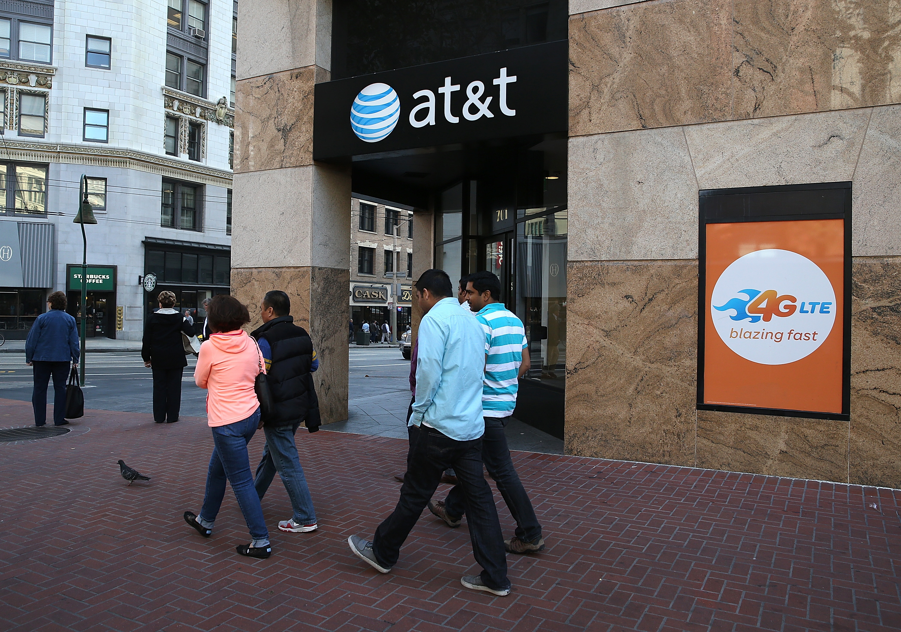 People walk by an AT&T store in San Francisco. (Getty)