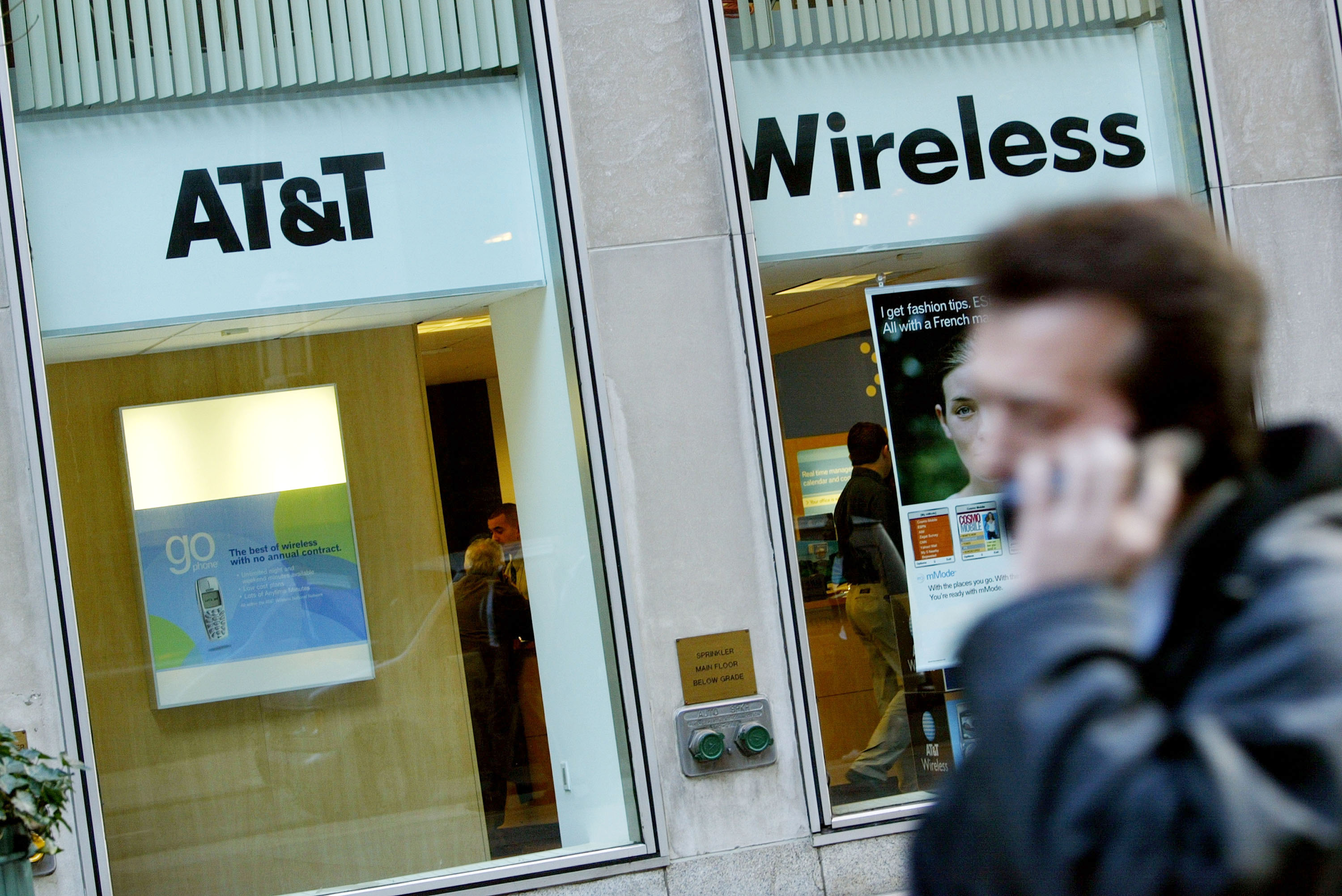 A person on a cell phone walks past an AT&T Wireless store in New York City. (Getty)