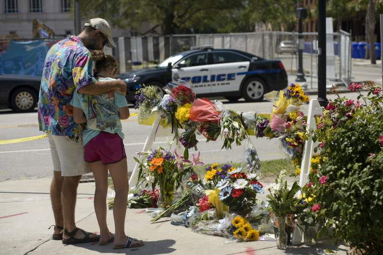 People visit a makeshift memorial near the Emanuel AME Church June 18, 2015 in Charleston, South Carolina, after a mass shooting at the  Church on the evening of June 17, 2015.  US police on Thursday arrested a 21-year-old white gunman suspected of killing nine people at a prayer meeting in one of the nation's oldest black churches in Charleston, an attack being probed as a hate crime. The shooting at the Emanuel African Methodist Episcopal Church in the southeastern US city was one of the worst attacks on a place of worship in the country in recent years, and comes at a time of lingering racial tensions. AFP PHOTO/BRENDAN SMIALOWSKI        (Photo credit should read BRENDAN SMIALOWSKI/AFP/Getty Images)