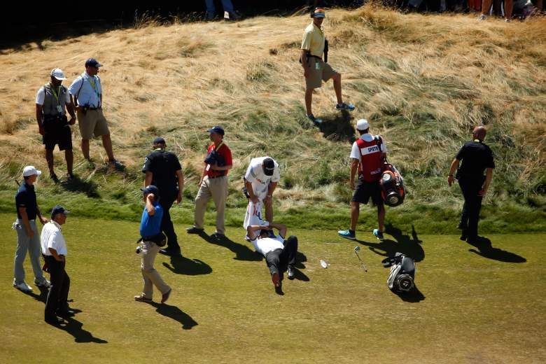 Jason Day is attended to on the 18th fairway after collapsing Friday in the US Open. (Getty)